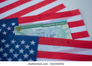 Permanent Resident Green card  of United states on flag of USA surface.