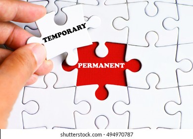 """PERMANENT"" word on missing puzzle with a hand hold a piece of ""TEMPORARY"" word puzzle want to complete it - business and finance concept"