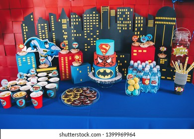Perm/Russia - April, 25, 2018: Delicious sweet buffet with cake. Spiderman, Superman, Batman  Candy Bar. Many red, blue and yellow balloons decorated wall. Birthday party.