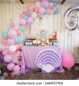 Perm/Russia - June, 28, 2019: Mermaid Candy Bar. Delicious sweet buffet with cake. A beautiful buttercream cake decorated with mermaid tails. Design of balloons. Children Birthday party.