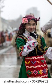"PERNIK, BULGARIA - JANUARY 26, 2014: A young girl in a traditional Balkan costume smiling during a traditional Bulgarian festival for banishing evil spirits called ""Surva""."