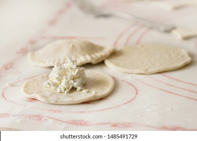 Perogies (varenyky) being prepared with dry cottage cheese and pinched together with fork; cooking varenyky from scratch and stuffing the pockets with cheese