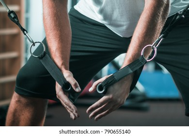 Peronal trainer with male client exercising in the gym