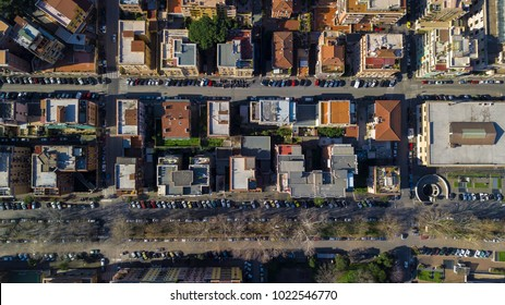 Perpendicular aerial view of a group of buildings in the Tuscolana district in Rome, Italy. All the roofs are walkable and full of antennas and TV dishes. down the streets lit by the sun.