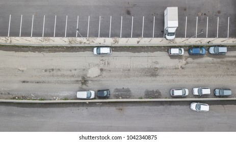 Perpendicular aerial view of a road. nobody is on the street. There are only a few cars and vans parked on the asphalt ruined by the holes.