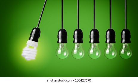 Perpetual motion with light bulbs and energy saver bulb. Idea concept on green background.