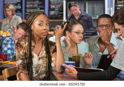 Perplexed beautiful African student studying with friends