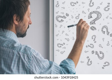 Perplexed businessman drawing question marks on whiteboard in the office, selective focus
