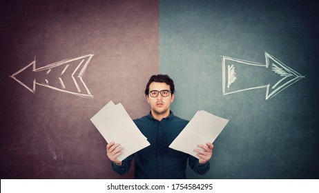 Perplexed businessman has to choose as holds different paper documents in both hands. Selecting the correct financial report, arrows shows left and right sides. Difficult decision, doubt concept.