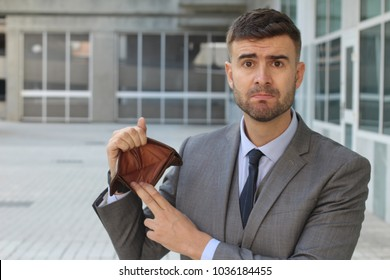 Perplexed businessman holding his empty wallet