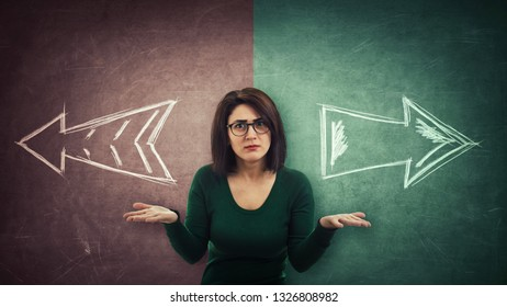 Perplexed businesswoman has to choose. Split blackboard and arrows going in two different ways red and green side. Correct choice between left and right, failure or success. Difficult decision concept