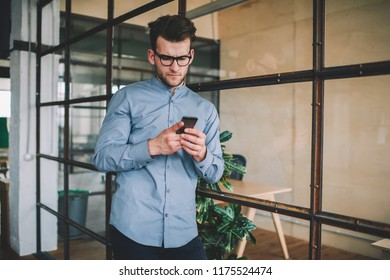 Perplexed caucasian man reading sms message via smartphone device browsing internet in office, confused hipster guy in eye wear watching online video connected to wifi via modern cellular phone