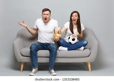 Perplexed couple woman man football fans cheer up support favorite team with soccer ball, hold glass bowl of chips isolated on grey background. People emotions, sport family leisure lifestyle concept