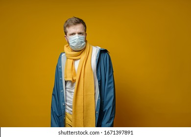 Perplexed man in a medical mask, looks anxiously at the camera. Copy space. Concept of the spread of the virus.