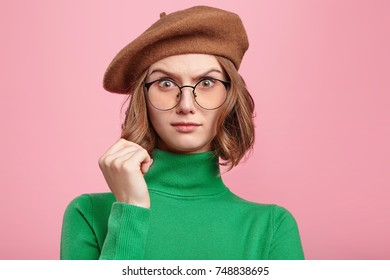Perplexed pleasant looking clueless female being in stupor as doesn`t understand question, has no answer, feels confusion, looks with bugged eyes through round glasses, isolated over pink background