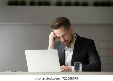 Perplexed, puzzled handsome businessman looking at laptop screen at workplace in office. Young CEO or project manager is not sure whether he should agree to the deal, sign contract, buy stock shares.