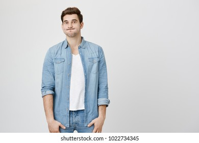 Perplexed and puzzled handsome guy, standing straight in denim clothes, puffing cheeks and starring at camera, over gray background. Son after huge party do not know how to clean all mess.