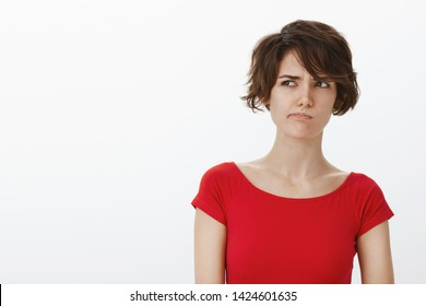 Perplexed unsure thoughtful cute pretty woman short haircut pondering difficult choice smirking frown look up squinting uncertain hesitating taking decision stand white background thinking