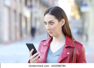 Perplexed woman checking smart phone news standing in the street