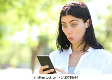 Perplexed woman reading smart phone content in a park with a green background