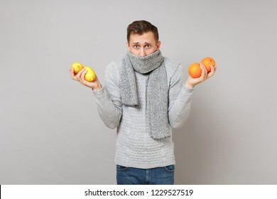 Perplexed young man in gray sweater covering mouth with scarf holding oranges, lemons isolated on grey background. Healthy lifestyle ill sick disease treatment cold season concept. Mock up copy space