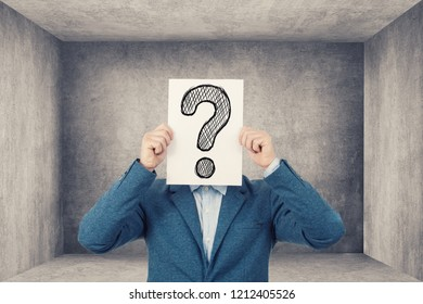 Perplexed young student businessman holding to white papers with question marks on his face in a closet room unknowing what to do.Stressed young man having to many questions.