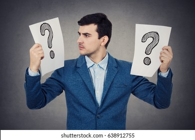 Perplexed young student businessman holding to white papers with question marks on them knowing what to do.Stressed young man having to many questions.