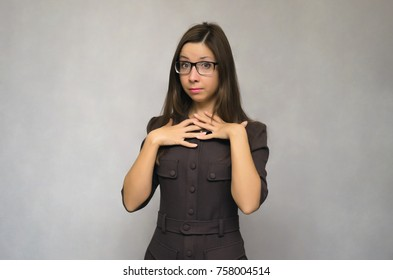 Perplexed young student girl is confused, justified and proves that she is not guilty of anything. Quandary. Justification concept. It is not me concept.