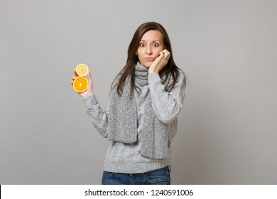 Perplexed young woman in gray sweater, scarf put hand on cheek hold lemon orange isolated on grey background. Healthy fashion lifestyle people sincere emotions cold season concept. Mock up copy space