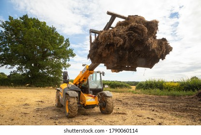 Perry Green, Much Hadham, Hertfordshire. England. UK. August 4th 2020. Farmer using a telehandler with a muck fork full of manure.
