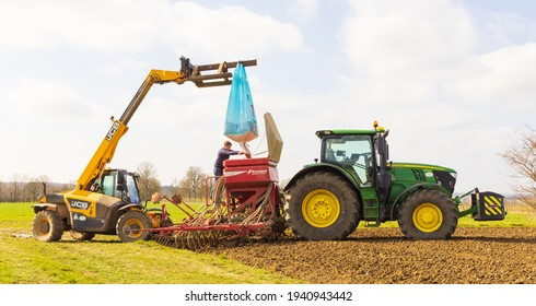 Perry Green, Much Hadham, Hertfordshire. UK. March 22nd 2021. Farmer with a telehandler loading seeds into a seeder driller attached to a tractor.