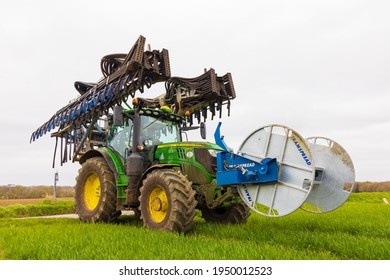 Perry Green, Much Hadham, Hertfordshire, UK. April 3rd 2021. Tractor with a folded Tramspread slurry spreader Dribble Bar and mounted hose reeler, used to apply slurry to fields.