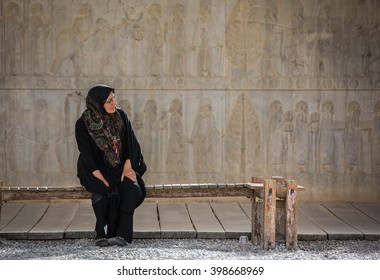 PERSEPOLIS, IRAN - CIRCA APRIL 2015: lady in traditional clothing sitting on a bench in front of ancient carved wall