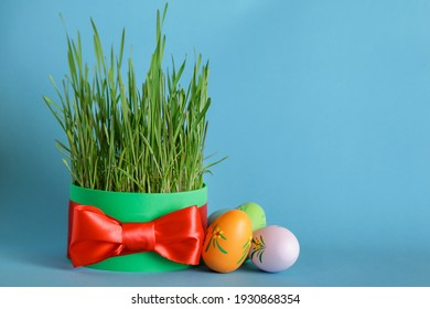 Persian, Azerbaijani Nowruz. Novruz celebration. Wheat grass, eggs on blue background, Copy space. Easter theme, red ribbon, spring equinox greeting card.