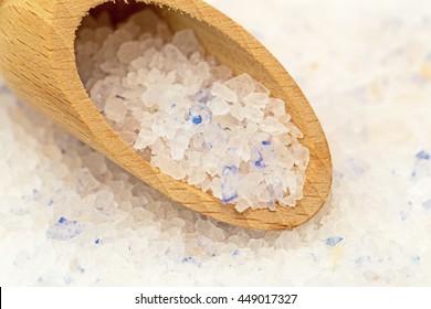 Persian blue rock salt crystals in wooden spoon on blue salt background, close up
