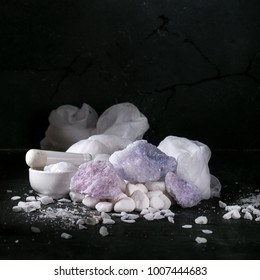 Persian blue salt decorated with napkin, olive oil and chili oil over a rustic stone background. Copy space. Square image