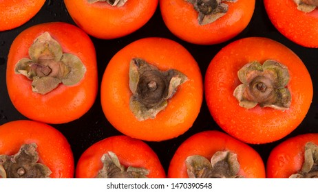 Persimmon background. Red ripe persimmon top view. Persimmon fruit close-up.