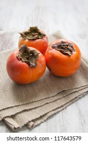 Persimmon fruit on beige cloth over white wood