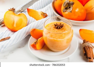 Persimmon fruit smoothie with cinnamon and anise stars, white marble table copy space