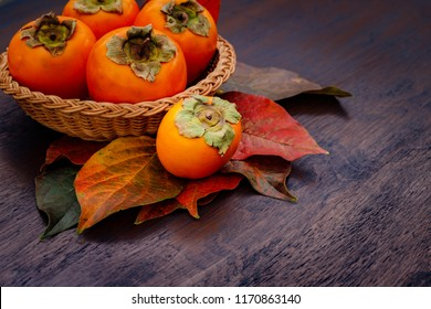 Persimmon fruits in basket and persimmon colored leaves on wooden background, top view.