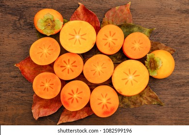 Persimmon fruits , cut in half, on persimmon leaves and wooden table background, top view