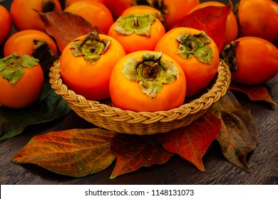 Persimmon fruits and persimmon  leaves in basket on wooden background