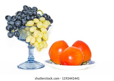 persimmon on a plate and grapes in a vase
