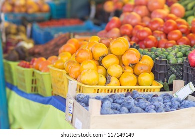 Persimmon, plums, tomatoes and other vegetables on city market