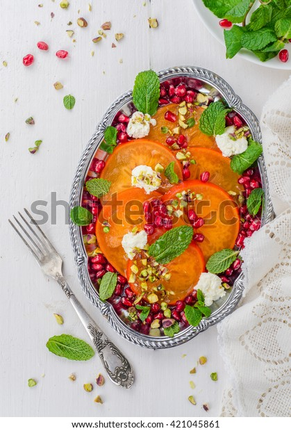 Persimmon salad with pomegranate cheese, pistachio and honey in metal vintage tray on white wooden background. Selective focus. Vertical top view