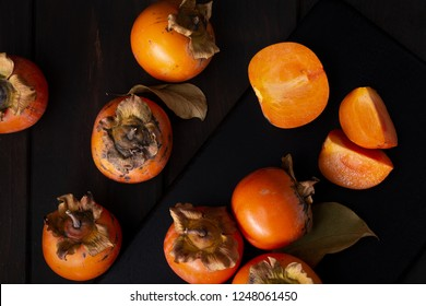 Persimmon still life in a low key. Organic Kaki fruit harvested in autumn. Top view. Diospyros kaki