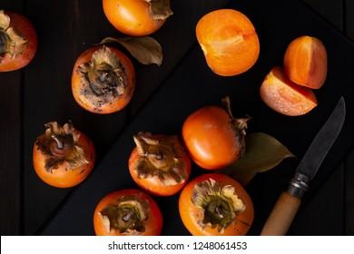 Persimmon still life in a low key. Organic Kaki fruit harvested in autumn. Top view. Diospyros kaki