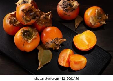 Persimmon still life in a low key. Organic Kaki fruit harvested in autumn. Diospyros kaki