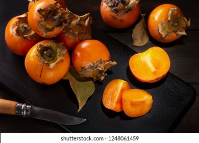 Persimmon still life in a low key. Organic Kaki fruit harvested in autumn. Diospyros kaki