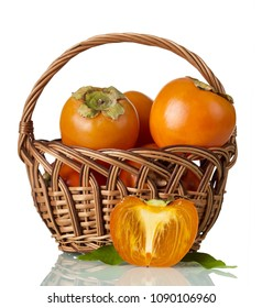 Persimmon in wicker basket, near half of fruit isolated on white